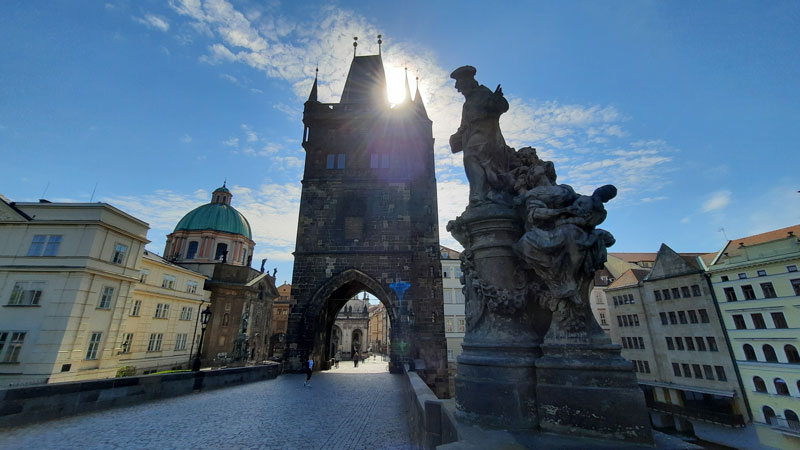 In the morning on Charles Bridge looking back towards the Old Town you see ST Francis church on the left, the old town gate tower is centre and a statue is on the right, blue sky and partly cloudy