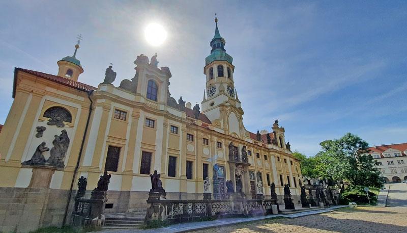 the yellow baroque style facade of the prague loreta