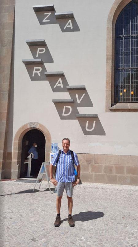man standing in front of a prague memorial to jan hus called za pravdu