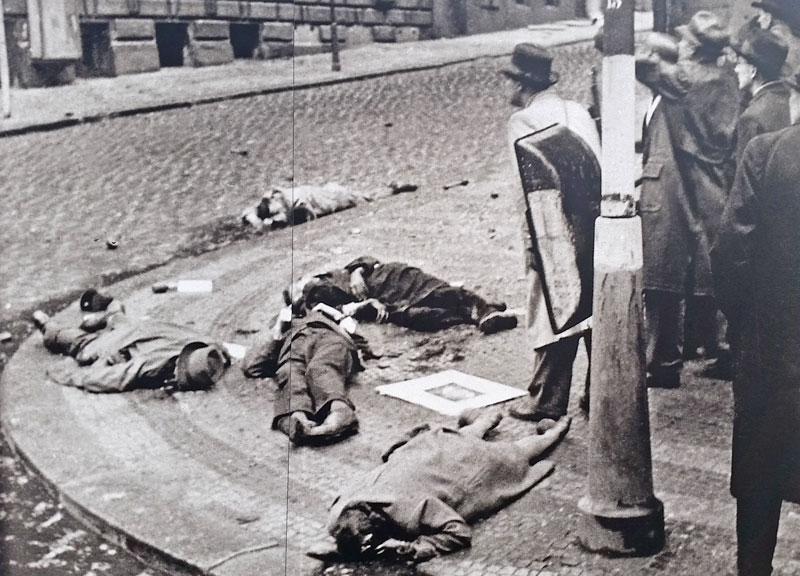 a black and white photo showing dead czech civilians on a street corner close to the radio station