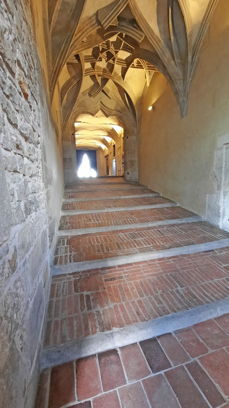 Prague Old Royal Palace Riders Staircase with shallow red brick steps and curved vaulted gothic ceiling