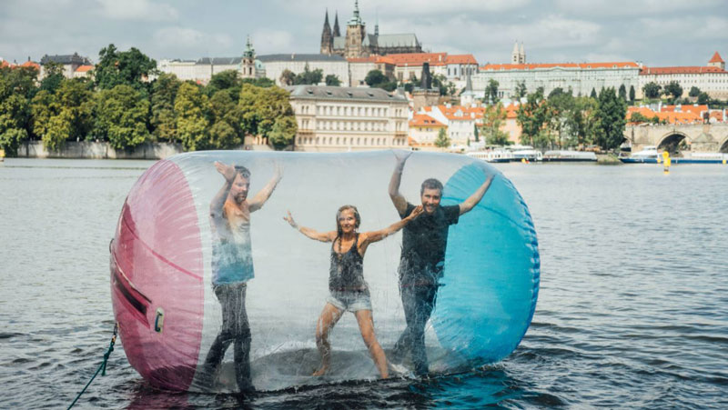 three people water zorbing in prague with the castle in the background