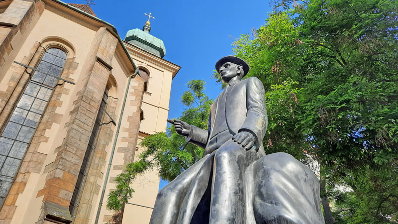 franz kafka monument in prague with background tree, blue sky and part of the facade of the holy spirit church