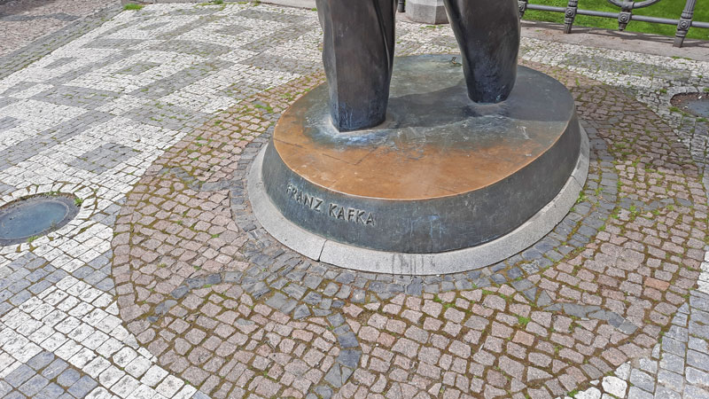 franz kafka monument in prague showing the cobble stone base with embedded shape of a gigantic insect