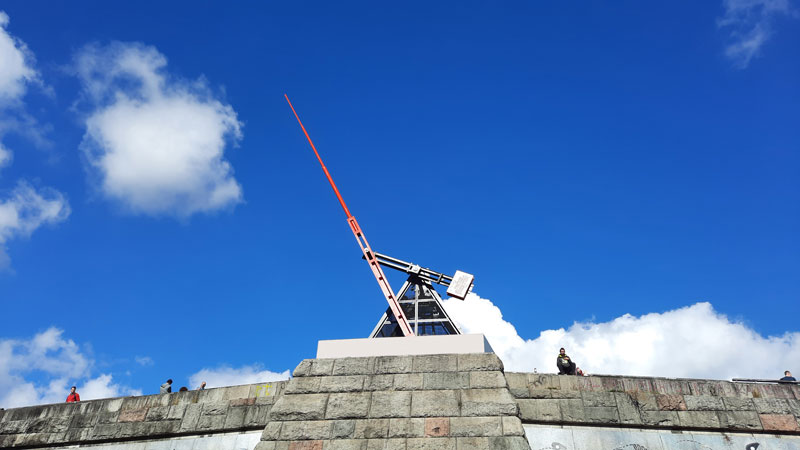 looking up at the prague metronome with blue sky and clouds
