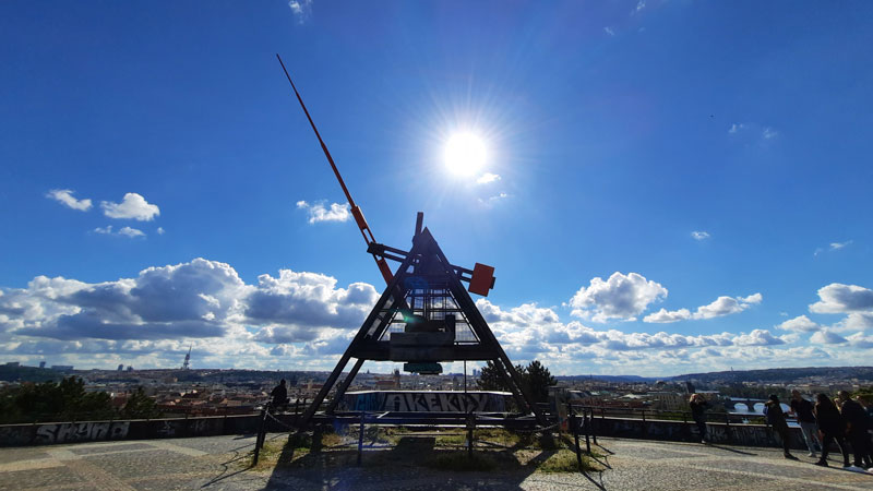 prague metronome in silhouette against a sunny blue sky