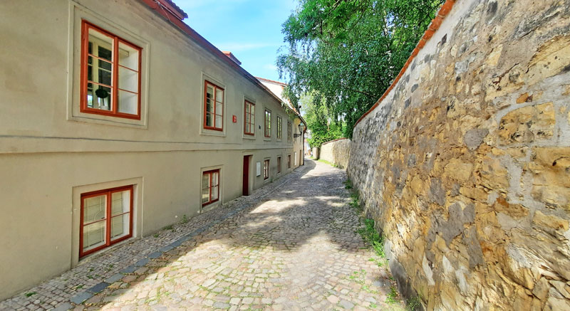 prague street called nový svět with stone wall and cobbled road