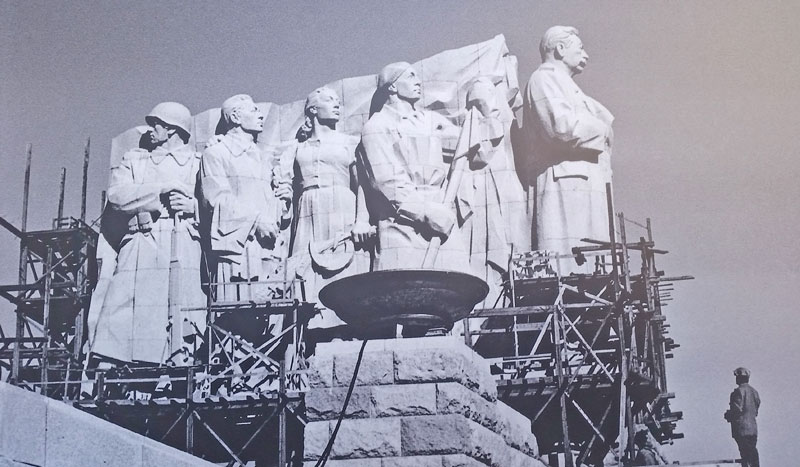 black and white photo showing the final construction of the prague stalin statue with nine characters made from granite stone
