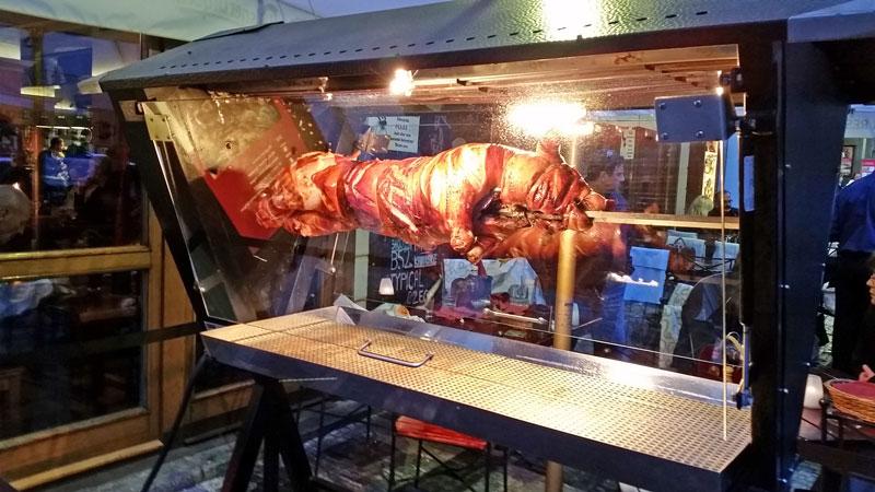 prague suckling pig roasting on a spit